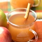 A cup of hot apple cider placed next to two apples