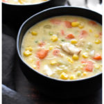 Thick chicken corn chowder with carrots and celery in a black bowl