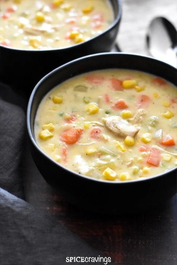 A bowl of gluten free chicken corn chowder served on a denim napkin