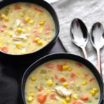 Two bowls of chicken corn chowder with carrots and celery