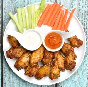 A plate of baked chicken wings served with hot sauce, ranch, carrots and celery These wings are spice rubbed, oven baked, or cooked in the Instant Pot,coated with spicy and delicious Buffalo sauce and grilled for a final tasty finish! #food #foodie #foodblogger #delicious #recipe #instantpot #recipes #easyrecipe #cuisine #30minutemeal #instagood #foodphotography #tasty