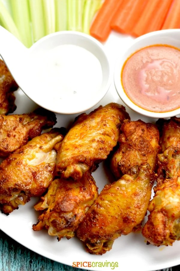 Buffalo Chicken wings on a white place with ranch and hot sauce
