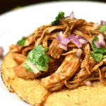 A plate of shredded salsa chicken tacos garnished with onion and cilantro