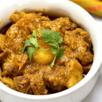 Indian spiced goat curry with potatoes garnished with cilantro