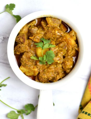 Indian spiced goat curry garnished with a cilantro sprig
