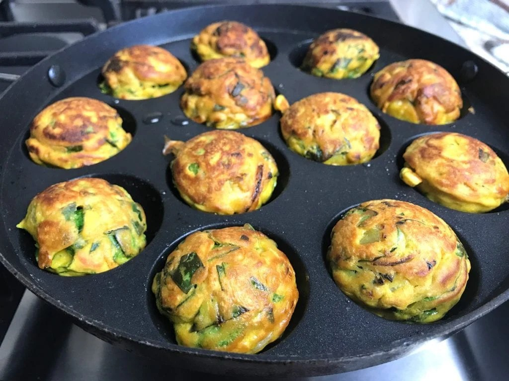 Onion spinach pakoras or fritters being made in a pan, without frying