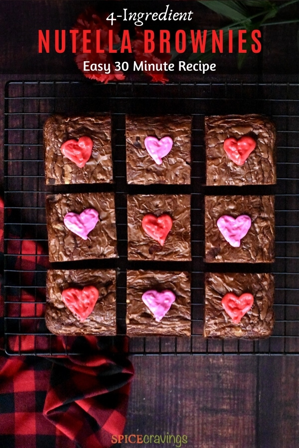 Chocolate brownies decorated with red and pink hearts resting on a cooling rack