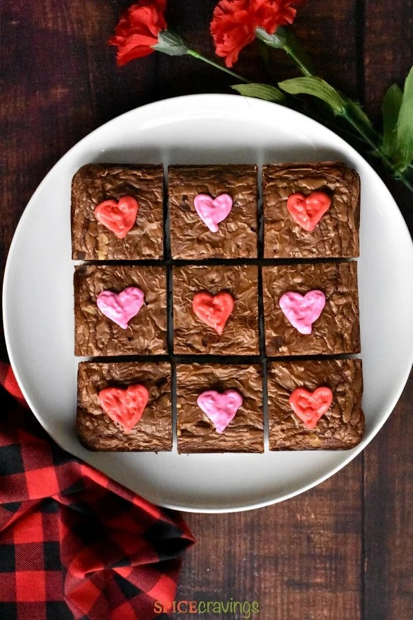 A white plate with Chocolate Brownies decorated with heart shaped icing for Valentine's Day