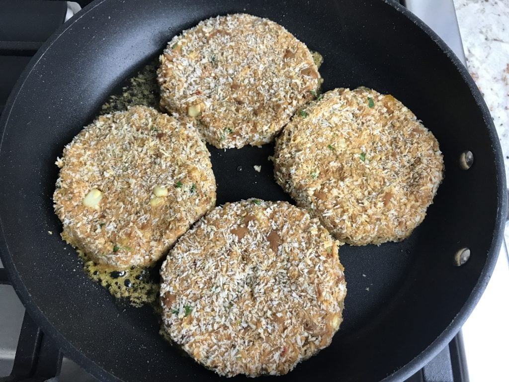 Bean burger patties placed in a skillet for cooking