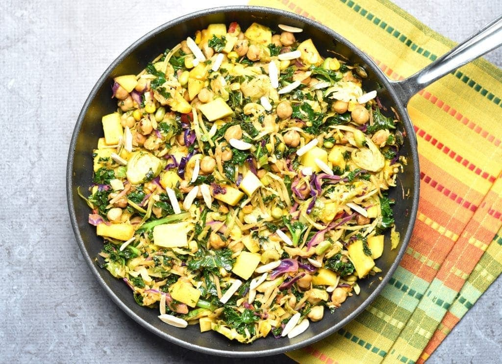 Kale mango slaw with chickpeas, made by sauteing kale slaw mix (from Trader Joe's), with chickpeas, juicy mango, and topped with crunchy slivered almonds. by Spice Cravings. #cooking #food #recipe #recipes #foodphotography #foodblogger #yummy #delicious #foodie