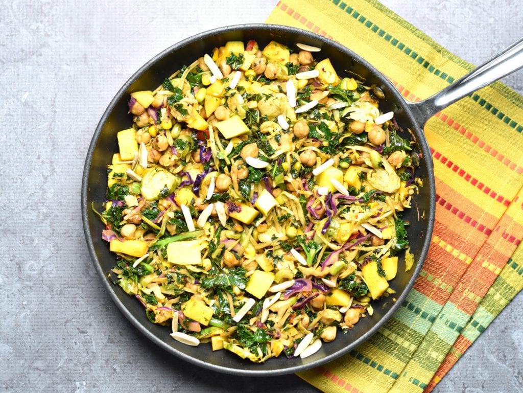 Kale and Mango Slaw with Chickpeas, made by sautéing kale slaw mix (from Trader Joe's), with chickpeas, juicy mango, and topped with crunchy slivered almonds. by Spice Cravings. #cooking #food #recipe #recipes #foodphotography #foodblogger #yummy #delicious #foodie