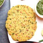 Makki Ki Roti, seasoned cornmeal flatbread, served with spiced mustard greens called Sarson Ka Saag, on a white plate