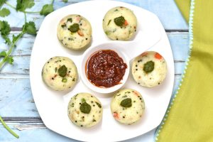 Instant Pot Rava Idli, savory steamed semolina cakes by Spice Cravings. These idlis made with rava, with mixed in corn, peas, carrots, and cashews. These rava idlis are soft and spongy and a real favorite with my kids. Made with semolina flour called Rava,this dish is a variation of the popular south-Indian breakfast dish called 'Idli' (steamed rice & lentil cakes). #cooking #food #recipe #recipes #foodphotography #foodblogger #yummy #delicious #foodie