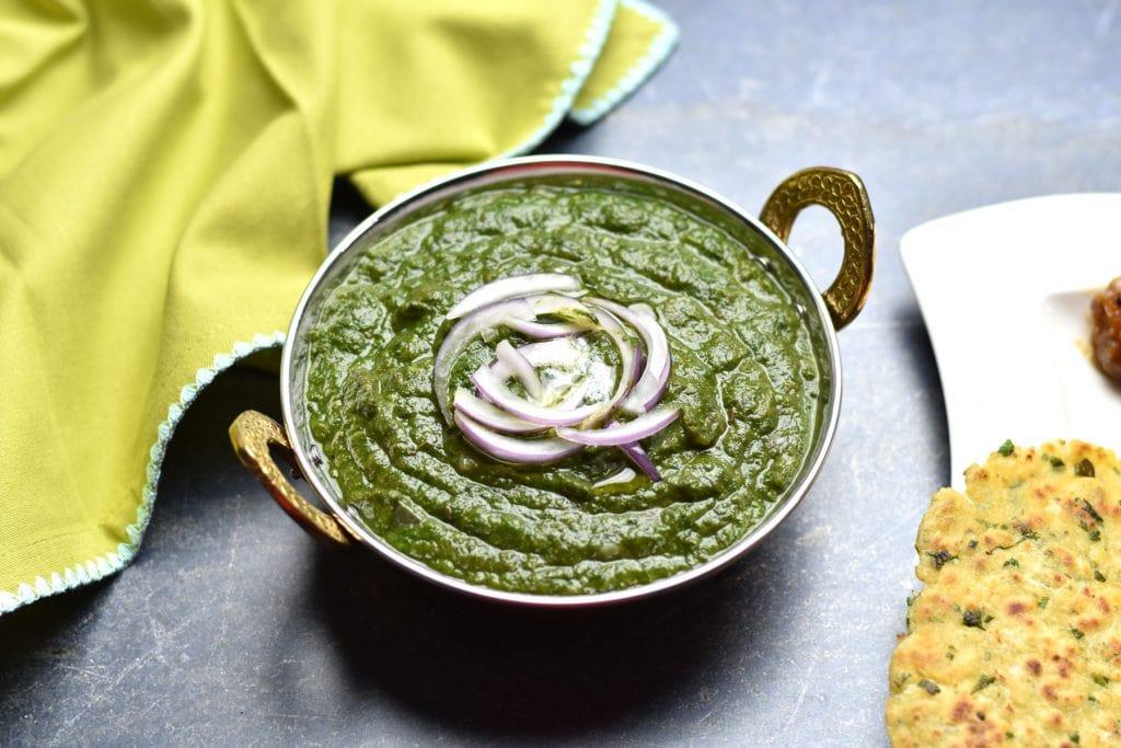 A metallic bowl with Instant Pot Saag (Sarson ka Saag), spiced mustard greens