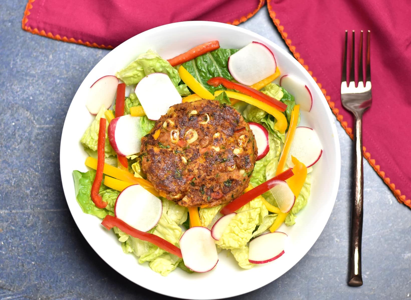 Veggie Bean Burger served over a bowl of salad