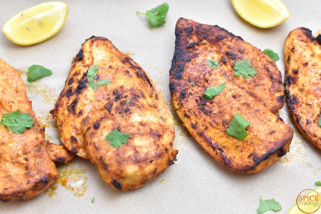 spiced grilled chicken with cilantro and lemon wedges