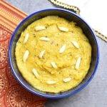 Kesar Badam Halwa garnished with slivered almonds served in a blue bowl
