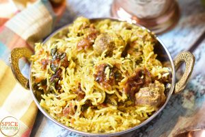 Indian spiced lamb and rice pilaf called Lamb Biryani, served in a copper bowl