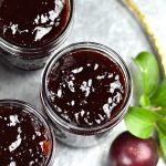 Plum jam in mason jars placed on a silver charger plate