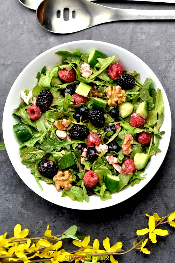 berry arugula salad tossed with strawberry vinaigrette in white bowl with serving spoons