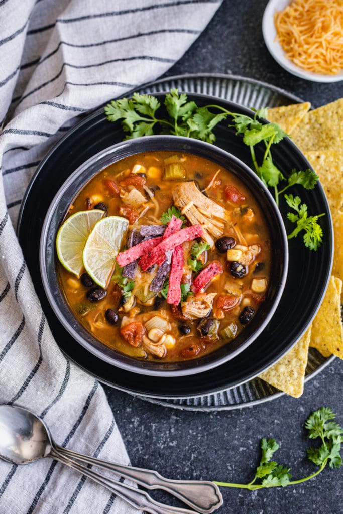 Instant pot chicken tortilla soup served with tortilla chips and lime wedges