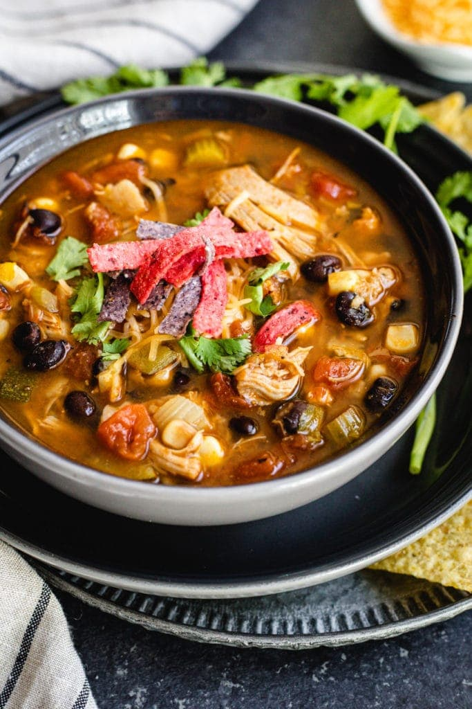 chicken tortilla soup in black bowl with cilantro sprigs and tortilla chips