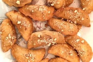Deep Fried Gujiya, by Spice Cravings. Deep Fried Gujiya, or Milk Fudge Turnovers, are a popular dessert made in the northern part of India around the festivals of Holi and Diwali. It is a deep-fried sweet dumpling that is made by stuffing pastry dough with sweetened milk fudge (khoya), chopped nuts and coconut flakes and is glazed with a thick sugar syrup. #cooking #food #recipe #recipes #foodphotography #foodblogger #yummy #delicious #foodie