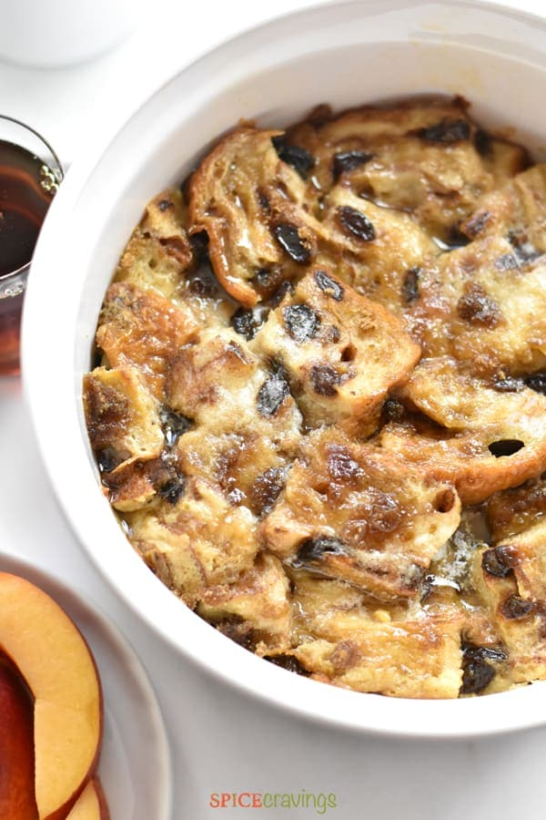 Baked French Toast Casserole served with maple syrup and sliced peaches
