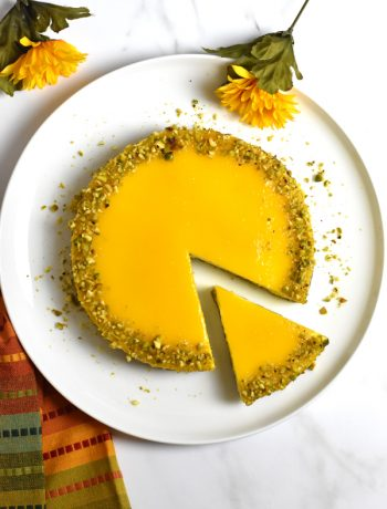 mango cheesecake garnished with crushed pistachio
