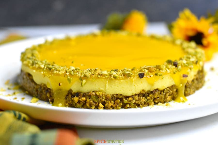 Side view of mango topping dripping on the sides of a Instant Pot mango cheesecake with pistachio crust