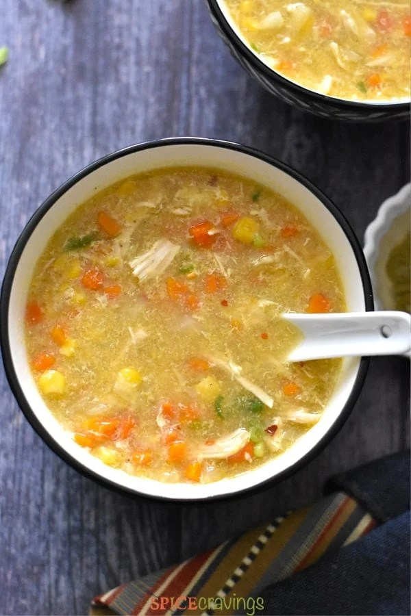 A bowl of Chicken Corn Soup with carrots and scallions