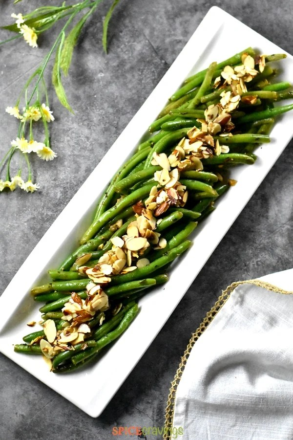 A white plate with crisp green string beans topped with almonds