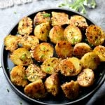 Golden crispy roasted potatoes seasoned with herbs and parmesan cheese, served in a black plate