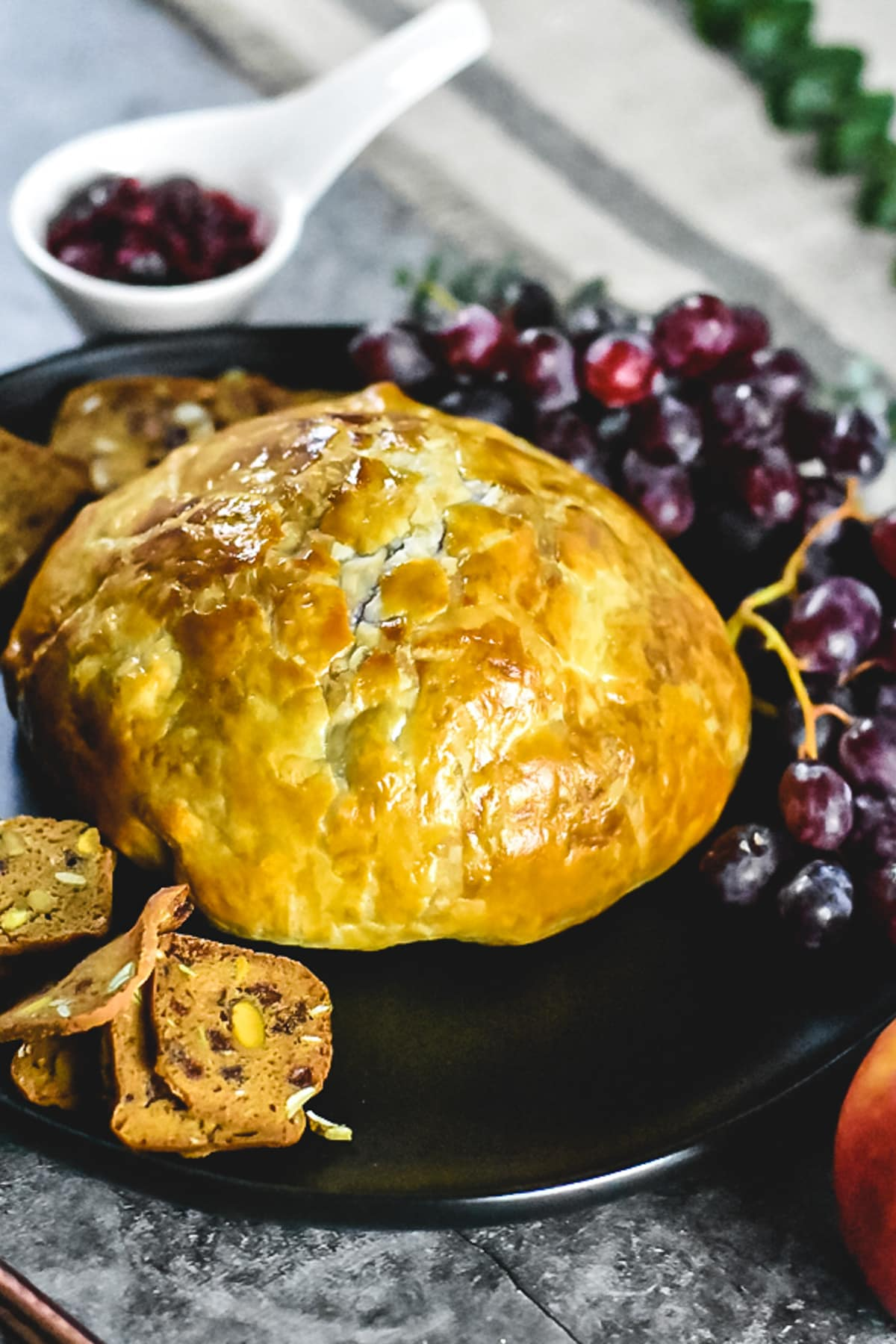 Baked brie in puff pastry served on a black plate with grapes and crackers