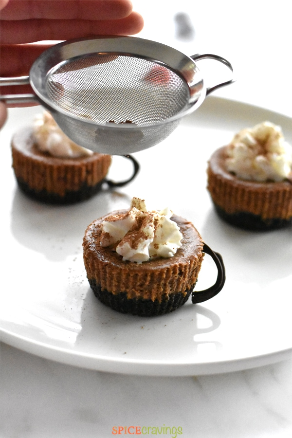 Mini Hot Cocoa cheesecakes on a white plate being dusted with cocoa powder