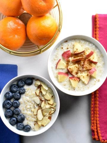 Two bowls of steel cut oats with assorted toppings
