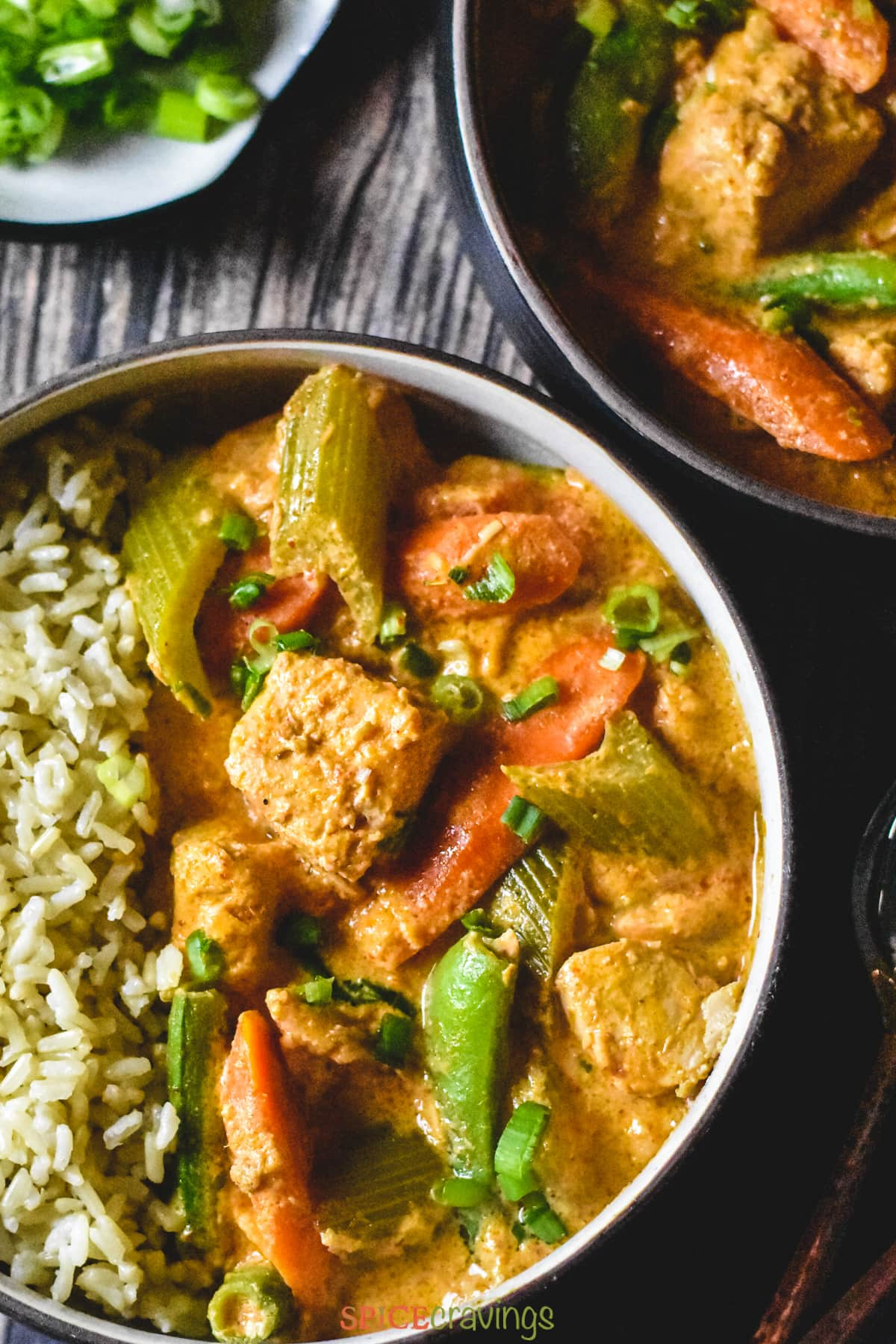 A spoon of thai red curry salmon with carrots and snap peas