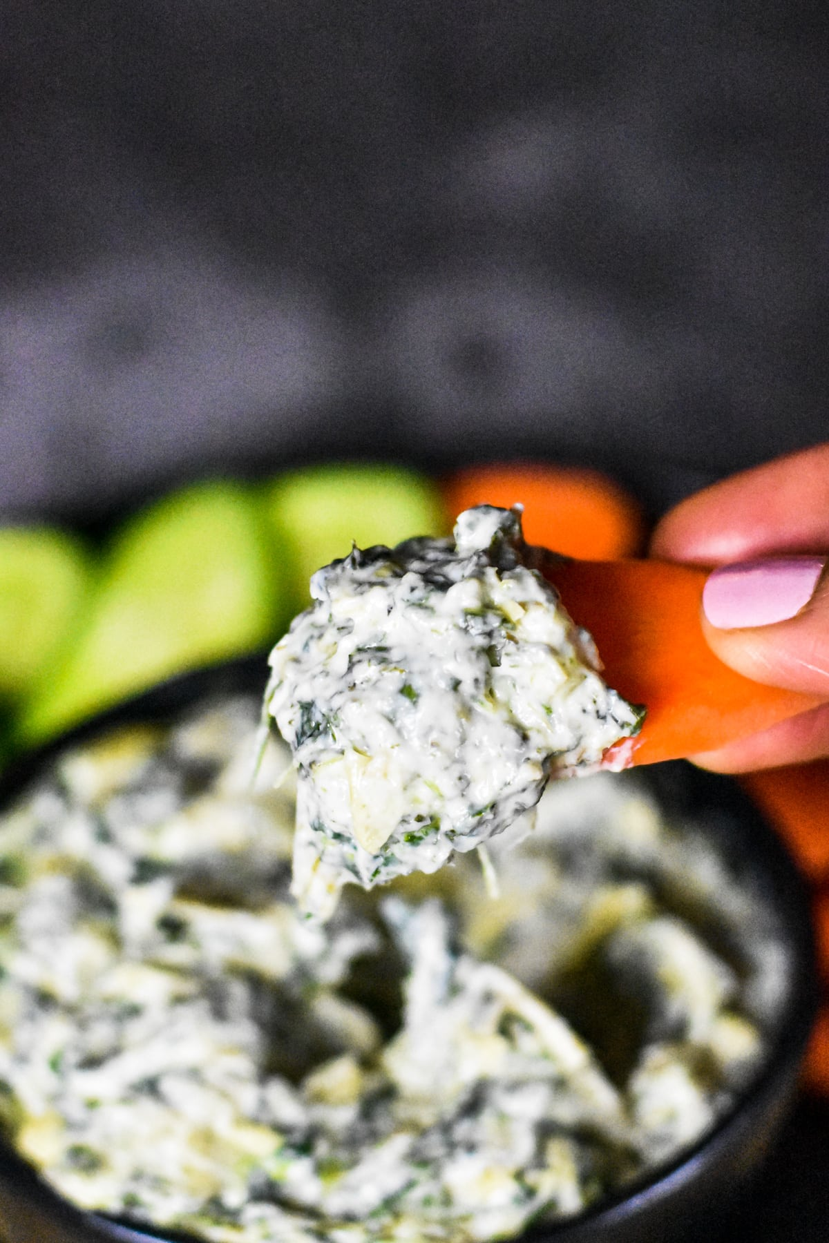 Dipping a carrot slice in creamy spinach artichoke dip