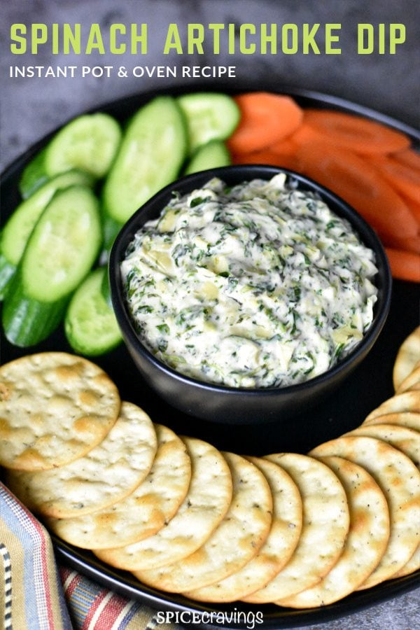 A bowl of spinach artichoke dip served with crackers, carrots and cucumbers