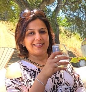 Picture of Aneesha sipping a glass of wine