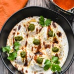 No fry Dahi Bhalle served in a bowl garnished with cilantro and chutney