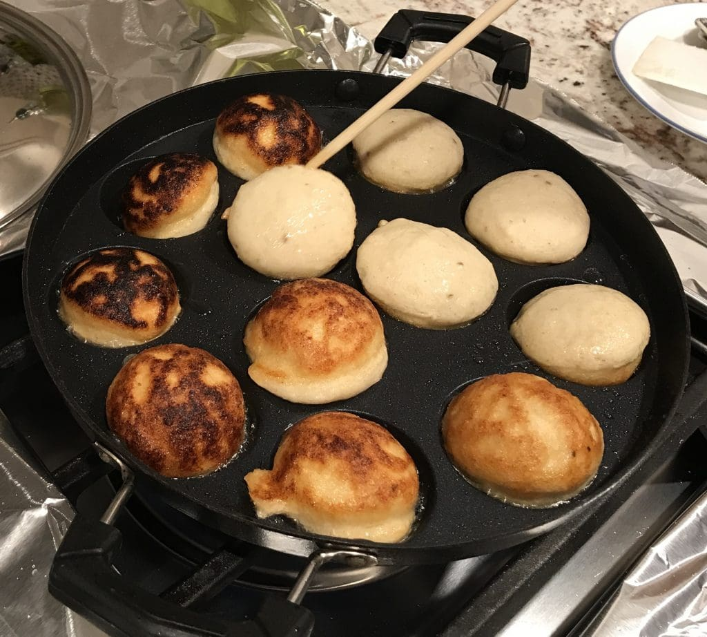 Flipping dahi bhalla in a stuffed-pancake pan