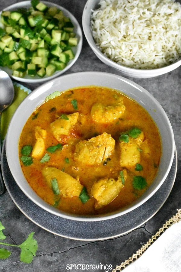 A grey bowl of Indian style Chicken Curry, with a side of cucumber salad and cumin rice