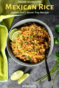 Colorful Mexican rice with corn and red peppers, garnished with cilantro and lime