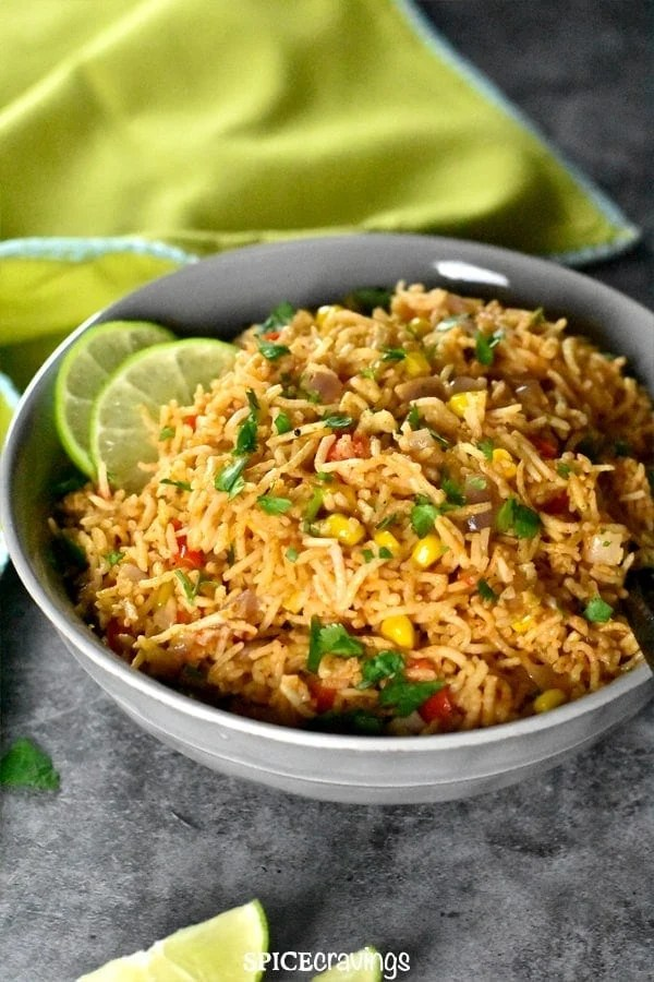 Colorful mexican rice served in a grey bowl with a lime green napkin