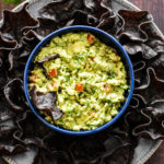 A bowl of fresg guacamole with blue corn chips served around