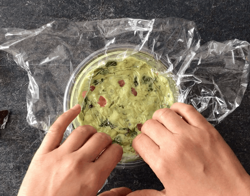 Pressing down plastic wrap to cover the surface of guacamole
