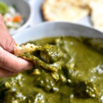 Scooping chicken saag with naan