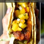 Grilled blackened fish tacos on a plate garnished with mango salsa