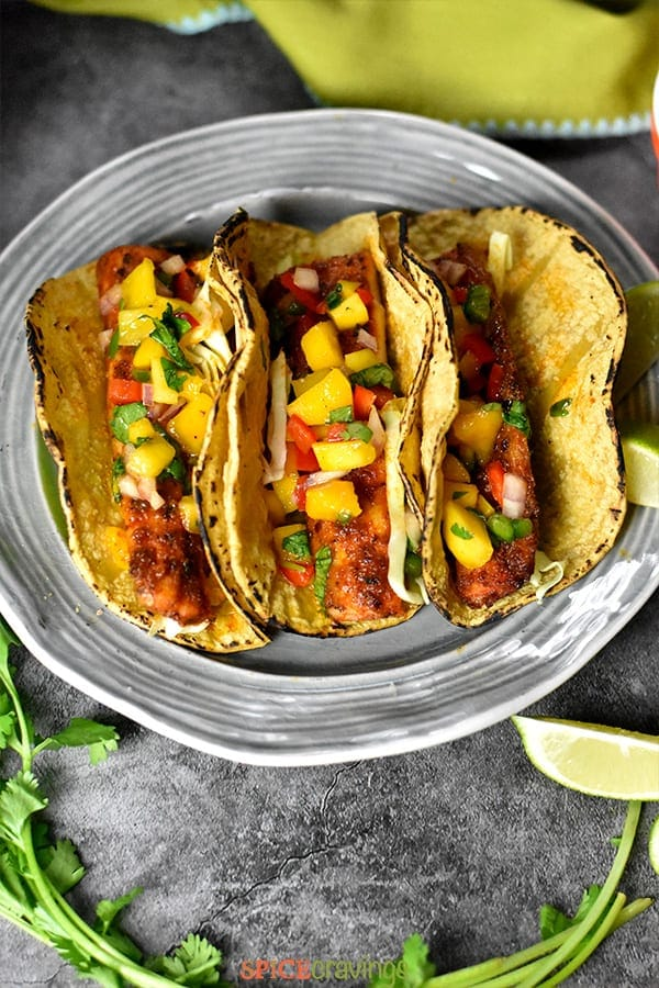 Three grilled corn tortillas with blackened fish topped with mango salsa